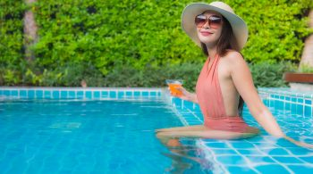 Portrait young asian woman relax happy smile around swimming pool in hotel resort